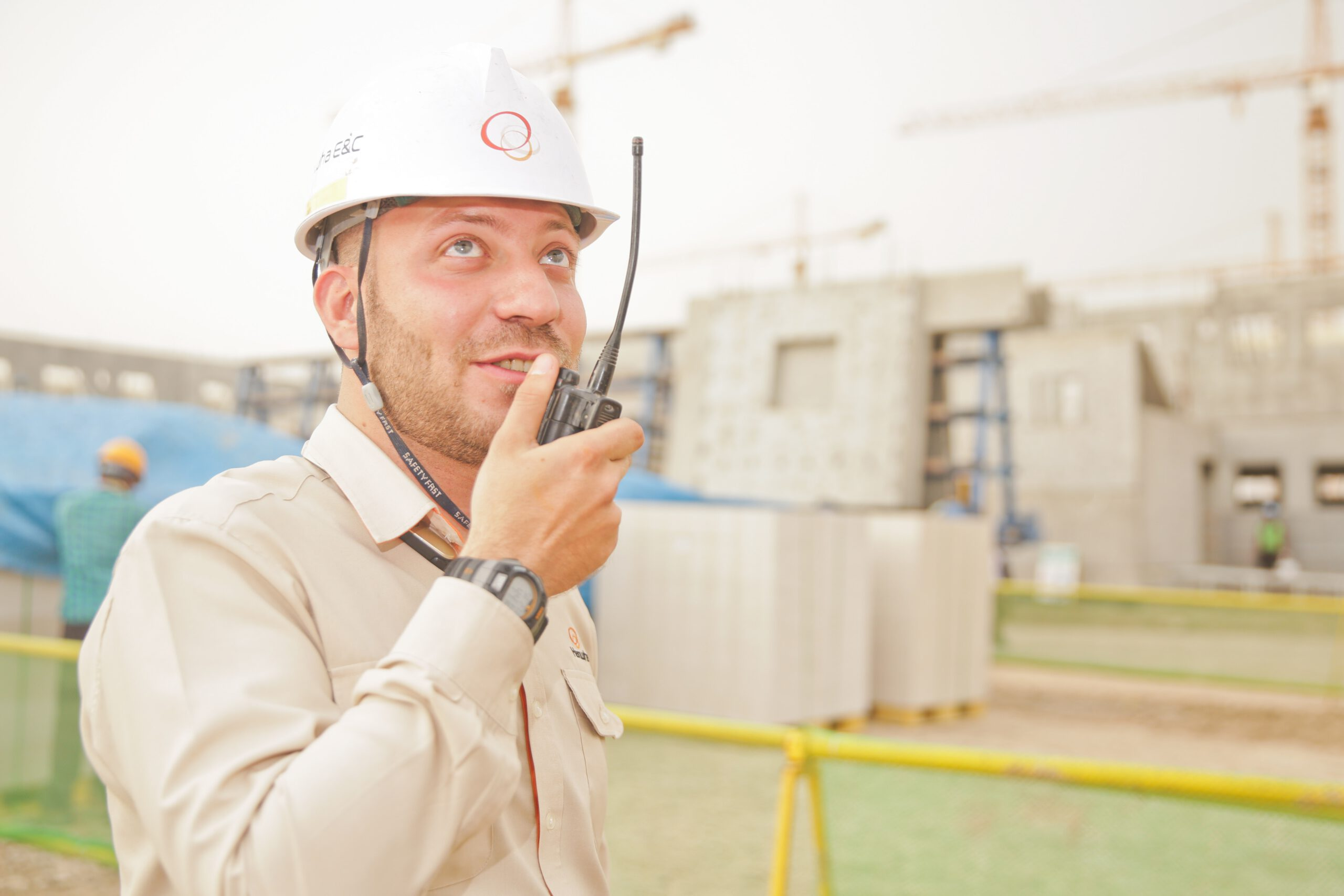 man-wearing-white-hard-hat-holding-2-way-radio-1078879
